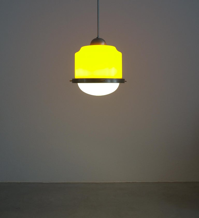 Stilnovo yellow glass pendant lamp glass, circa 1950  Beautiful Italian pendant light with a yellow glass shade and a white opal glass down light shade. Aluminum and steel hardware. It takes 3 e14 light bulbs, LED's are working also. It's in good