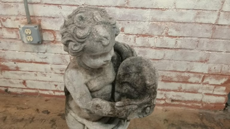 Stone Cherub holding oval tablet statue (late 20th century) originally made in England from reconstituted stone. Signed on back David Sharp & Co. Inc. Great vintage