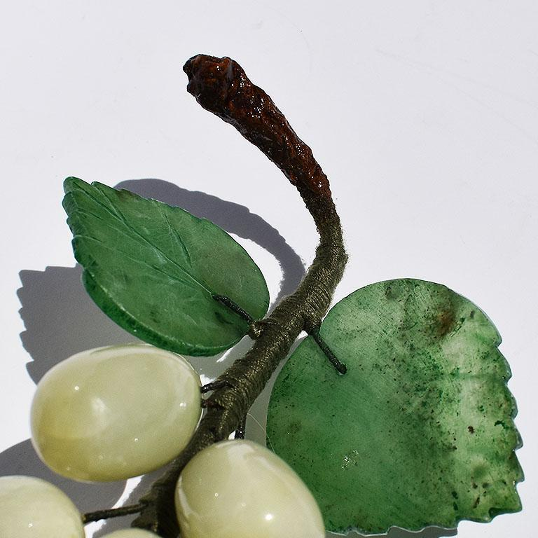 Cluster of carved stone grapes in a multitude of greens. A fabulous piece for accenting any table. This beauty features rounded oval carved grapes in green stone in a jade like hue. The cluster is tied together in green thread covered wire and