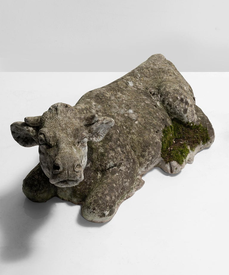 Composite sculpture of a cow lying down.