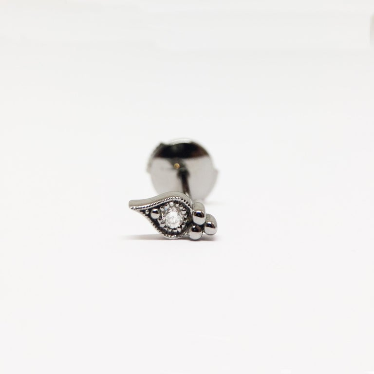 By Stone Paris  Button earring 18-kt black gold 0.62 g 1 GVS white diamond 0.03 ct Alpa system - Sold singly Size of the pattern : 0.4 x 0.9 cm  This piece is unavailable, it has to be especially handmade with an 8 to 10 weeks lead time.  All