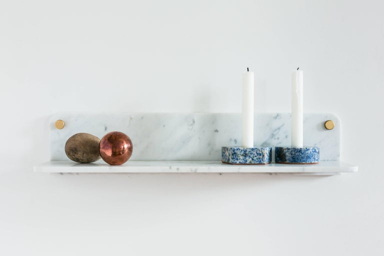 The thin stone elements of the wall-mounted shelf take advantage of the strength of Carrara marble to create a perfect touch to any room. Held to the wall by two solid brass thumbscrews, the shelf is easy to mount anywhere as an elegant accent or