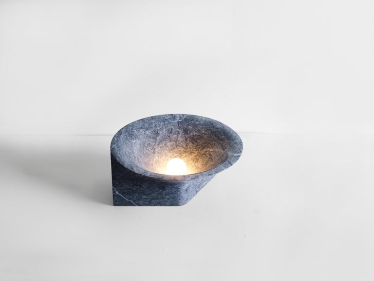 Stone uplight by Henry Wilson  The large stone uplight is carved from a single block of black travertine and emits an atmospheric glow. The sculptural form creates a balancing illusion.  Each light is manufactured in natural stone, meaning