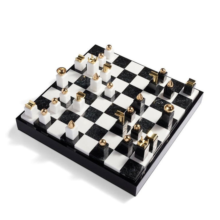 Chess stones game with black and white pieces made in stone with 24-karat gold-plated metal ornaments. Checkerboard made with black stone, white stone, black resin and wood. Checkerboard back case include parts to store pieces. Chess stones game