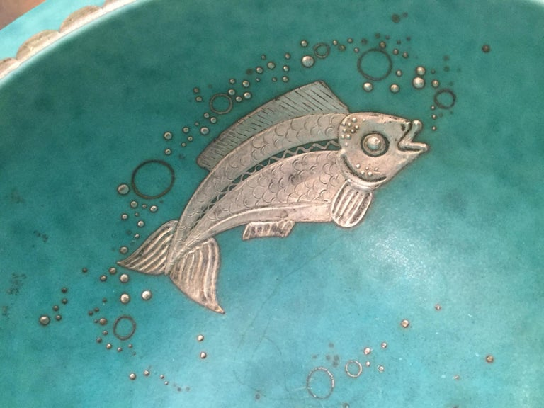 Stoneware bowl with an Evergreen glaze, the inside decorated with a silver fish and bubbles. Silver contributed by Argenta.