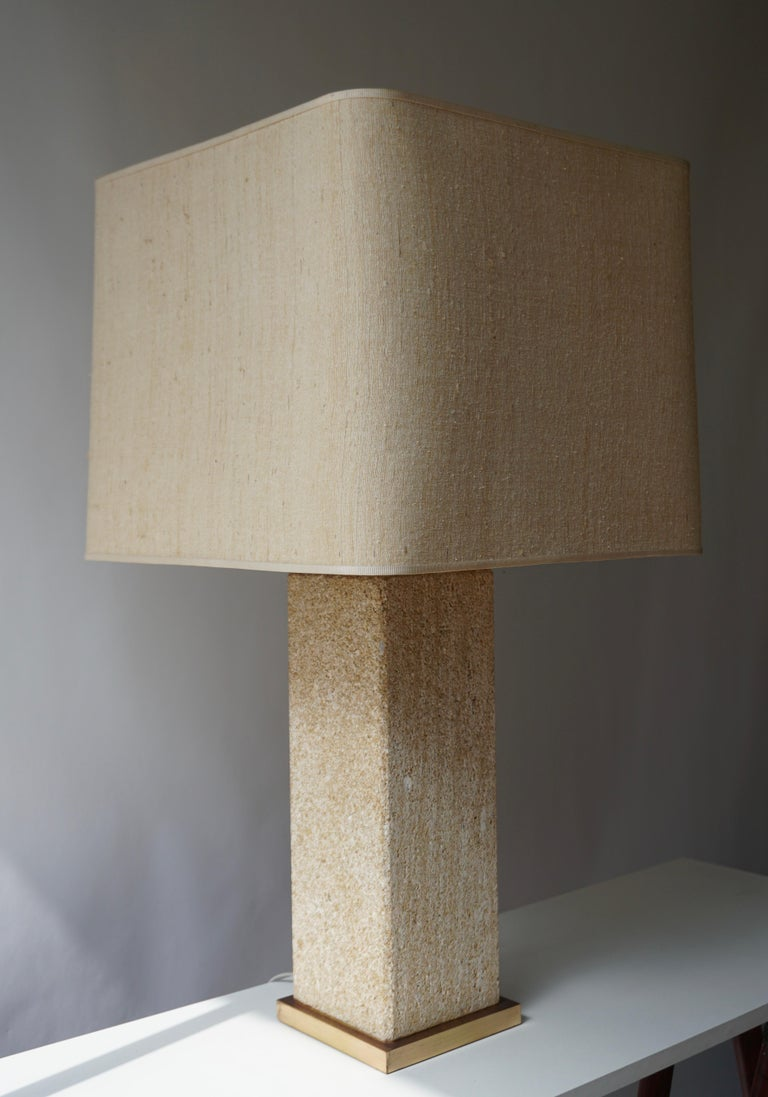Elegant table lamp in pressed in stone wear ceramic, Italy. The bottom border is in brass and with original shade.  Measures: Height max 97 cm. (min 88cm) Width base 15 cm. Width shade 46 cm. Weight 19 kg.