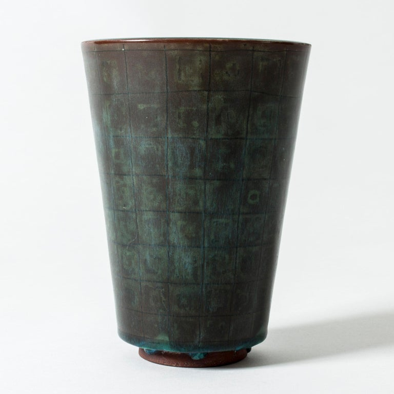 """Simple yet striking """"Farsta"""" vase by Wilhelm Kåge with clean lines and a subtle checkered pattern in the dark, patinated copper colored glaze. """"Farsta"""" stoneware is recognized as being the best and most exclusive that has come out of Swedish arts"""