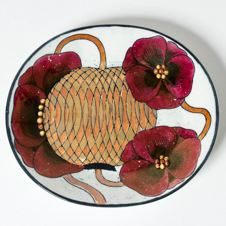 Unique stoneware platter by Birger Kaipiainen in an oval form. Striking motif of red flowers encircling a large seed pod with a graphic pattern in golden tones. Round seeds in the center of the flowers in relief.