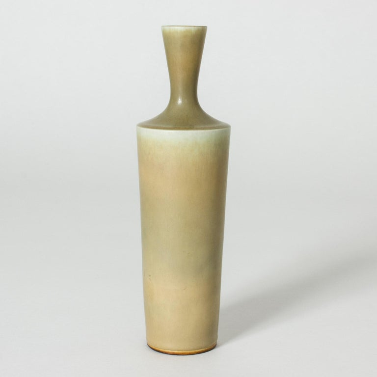 Stoneware vase by Berndt Friberg, in a stately shape with a sharp finish to the body where it transitions to the nozzle. Pale yellow hare's fur glaze.