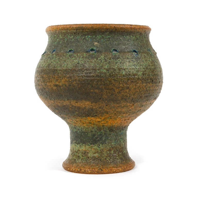 A Mid-Century Modern hand-thrown, studio-made footed stoneware vessel with a rustic and textured glaze. Made by Arabia in Finland, 1960s. Base diameter is 4.25