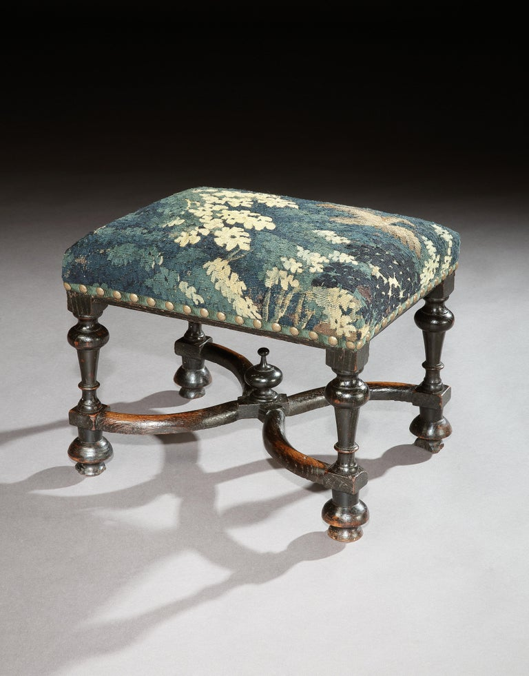 A rare, late 17th century. 'X' stretchered, ebonised, oak stool upholstered in 17th century verdure tapestry  This stool is sophisticated, elegant and refined and the flying bird on the tapestry is a charming and unusual feature. The fine turnings,