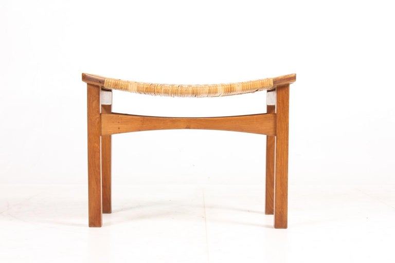 Rare stool in oak and seat in cane, designed by Ejnar Larsen and Aksel Bender Maden for Pontoppidan. Made in Denmark in the 1950s.