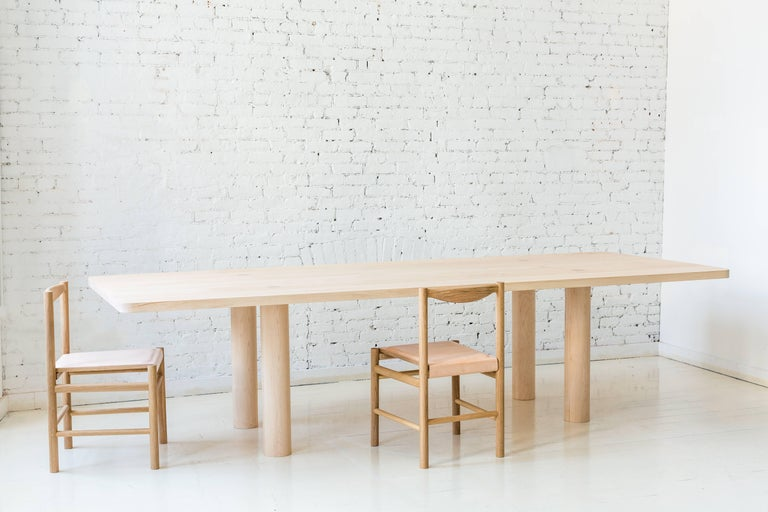 This contemporary, minimal dining table features a two inch thick hardwood top and four large round legs with no other structural base components. Each leg has a tenon that pierces the top, revealing the joinery. This subtle, important detail