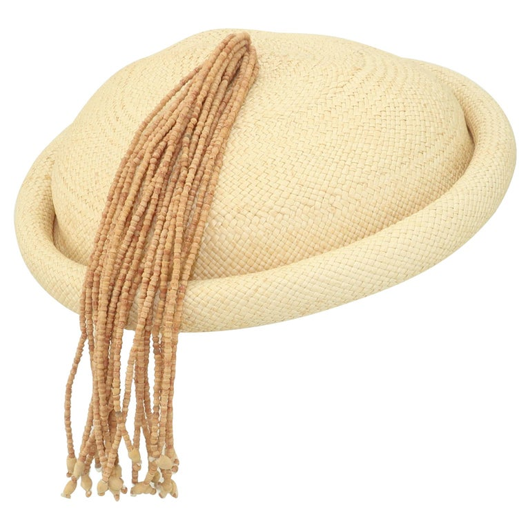A light natural straw disk shaped fascinator style hat with a wooden beaded tassel finial by Rosemary Peck.  Cute little topper for accessorizing your favorite tropical prints.  From the living estate of an amazing fashionista who was born in the