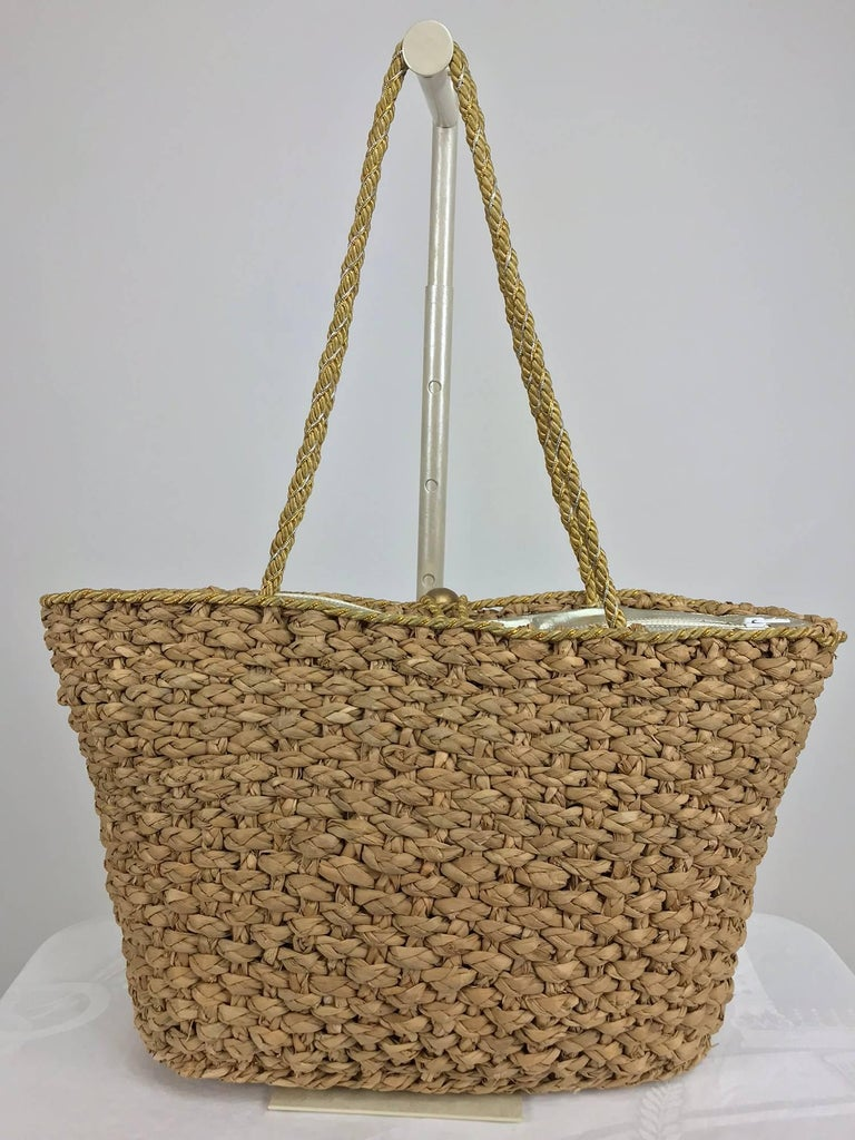Large natural straw tote bag with sea shells from the 1980s...Decorated with tassels and real sea shells (painted silver and gold, one has a little scratching see photos)...Silver top with zipper and cord loop and gold ball closure...Fully lined in