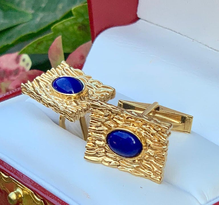 Striking pair of custom hand made mid century estate cufflinks are rectangular in shape and are made out of 14 Karat yellow gold. The richly textured bark finish beautifully compliments the bezel set oval shaped vivid blue lapis lazuli cabochons