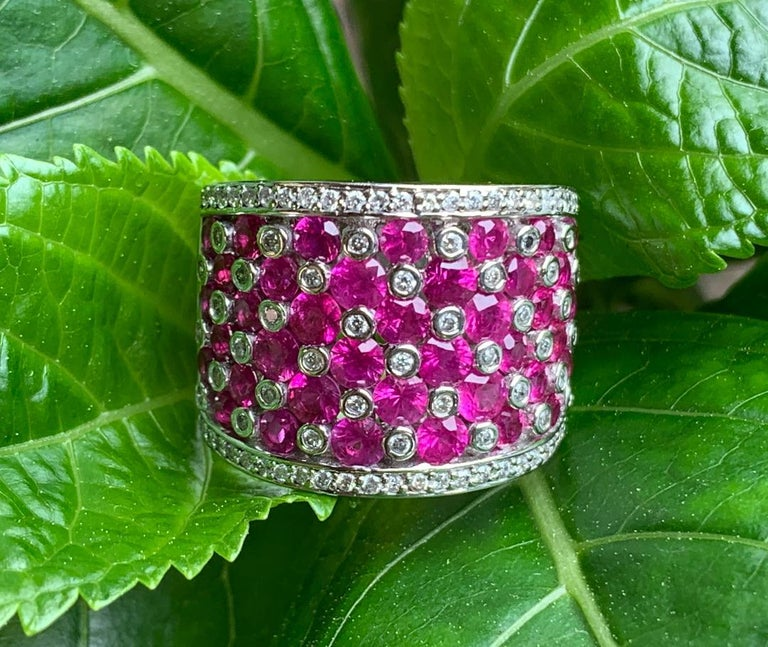 "Very stylish ladies 14 karat white gold designer ""Effy"" ruby and diamond wide band ring features a striking checkerboard design accented with a diamond border on the top and bottom.  Diamonds are bezel set and the rubies are invisibly set.  The"