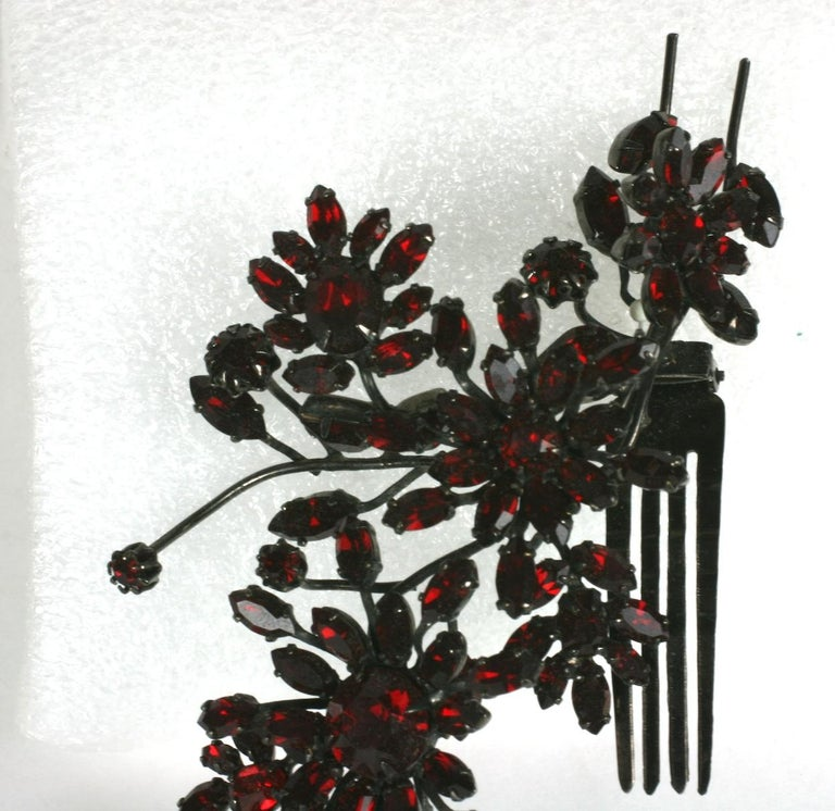 Striking Austrian Ruby Crystal Trembler Flower Hair Comb from the 1950's. Deep ruby Swarovski crystals are used for this floral hair comb/ornament and are striking set in deep gunmetal finish.  3 of the flowers are set in springs to tremble with