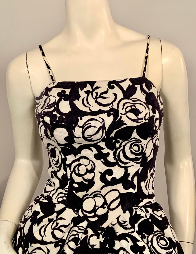This charming black and white floral print cotton pique summer evening dress will definitely get you noticed.   The dress has spaghetti straps, a fitted bodice with a V shaped, corset style seam above soft pleats in the full skirt.  The skirt gets
