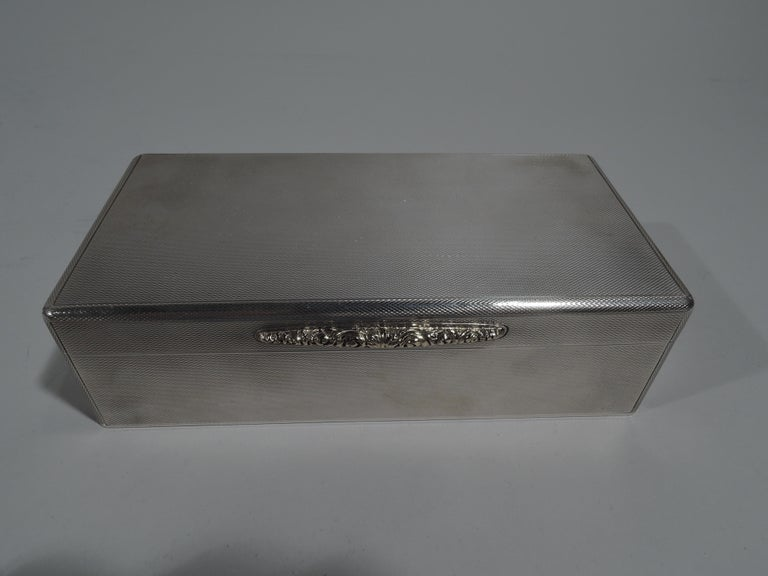 Edward VIII sterling silver box. Made by Padgett & Braham in London in 1936. Rectangular with straight sides and hinged and flat cover. All-over engine turned ornament. Tapering gold tab with tooled floral ornament. Box interior cedar lined and