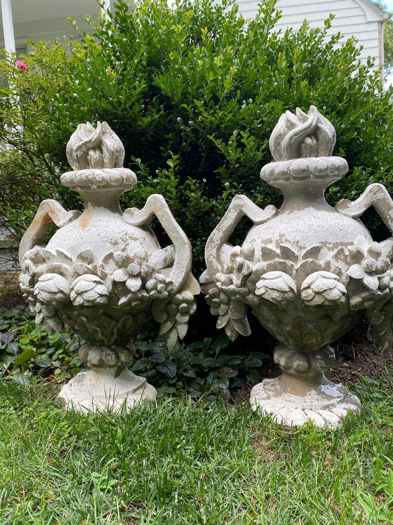 A charming pair of cast concrete garden decorations in the shape of neoclassical urns having roses on the body, handles and flame shaped finials. The urn shapes are hollow on the reverse sides and flat.