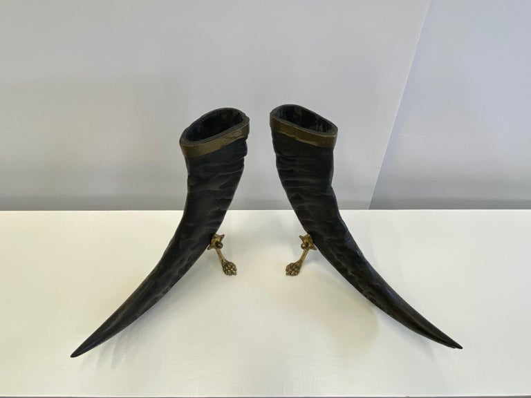 A fabulous pair of authentic sculptural buffalo horns having brass mounts around the tops and handsome brass bases with paw feet. An unexpected and beautiful masculine organic accessory.