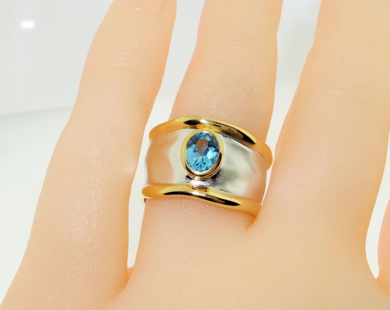 Beautiful solitaire ring featuring an oval Swiss Blue Topaz; approx. 0.71 carat; approx. stone size: 6mm x 5mm. Sterling Silver Tarnish-resistant Rhodium and gold accents on either side of mounting. Size 7. Classic and Chic…illuminating your look