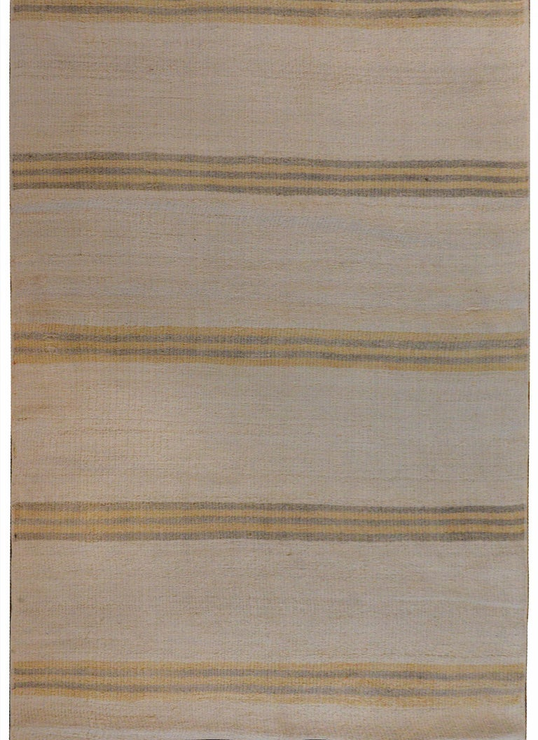 A striking vintage mid-20th century Turkish Konya Kilim runner with a gold and gray striped pattern on a cream colored background.