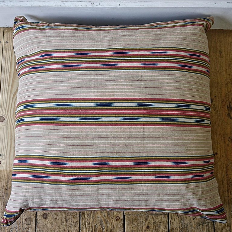 Late 19th century French floor cushion made from an interesting and unusual striped linen/cotton ticking with an indigo ikat detail. Stripes of faded beige, red and yellow with the indigo ikat floating in between. Backed in a vintage denim cloth