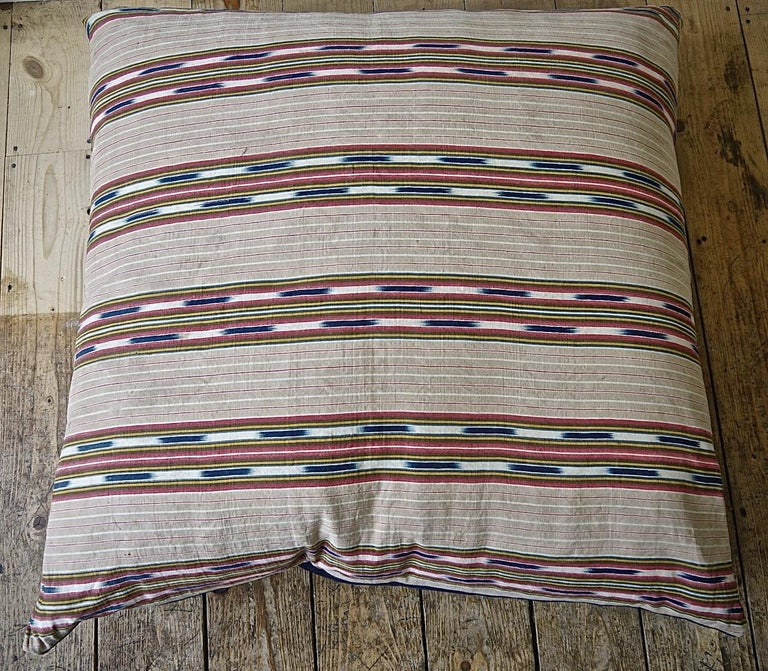 Late 19th century French floor cushion made from an interesting and unusual striped linen/cotton ticking with an indigo ikat detail.Stripes of faded beige, red and yellow with the indigo ikat floating in between.Backed in a vintage denim cloth with