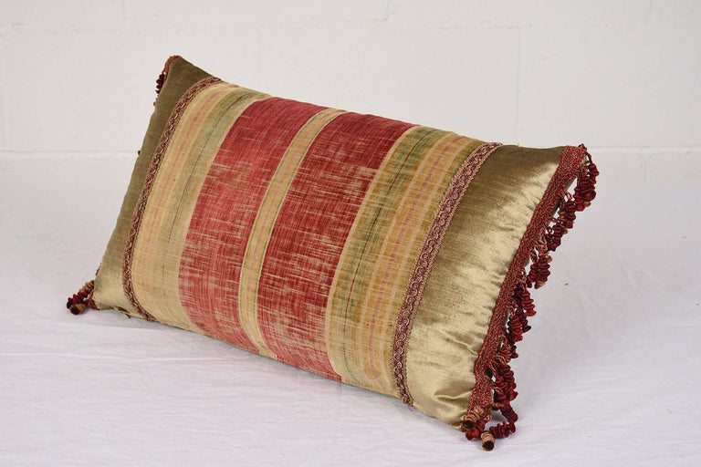 This throw pillow has an antique French textile panel on the front of stripes in varying shades of red, gold, and green. The sides and back of the pillow is upholstered in a sage green with gold accents velvet fabric. The edges of the pillow have