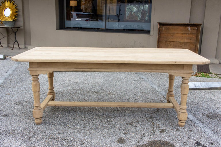 This antique French oak table has turned details in the legs, with hand carved accents in the apron and an I-shaped stretcher at the base. There are carved details in the apron, where the legs meet, at each corner. The top itself has a rounded edge
