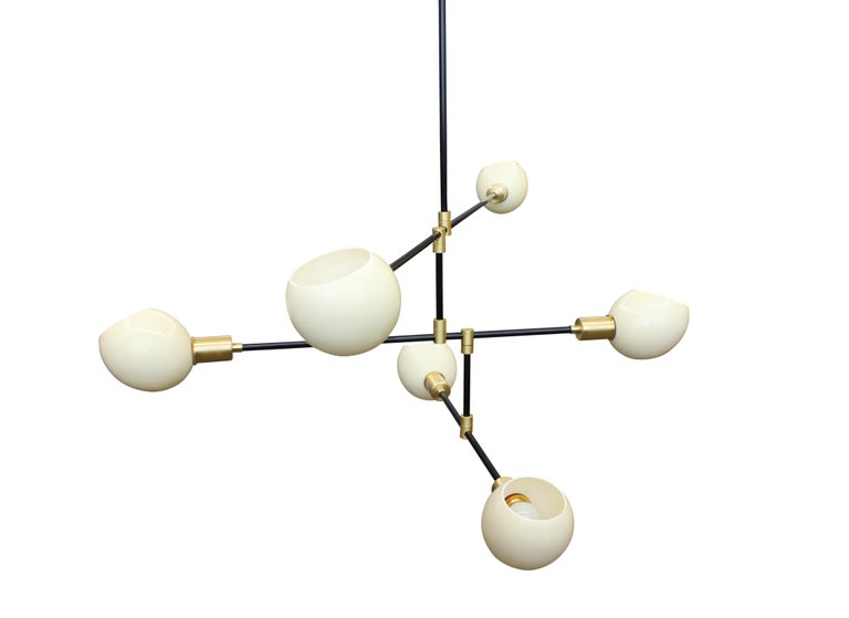 Six armed chandelier in blackened steel with brass fittings, featuring six bias cut natural ostrich egg diffusers. Adjustable arms can be arrayed at various angles. Can also be made as an eight or ten arm fixture.