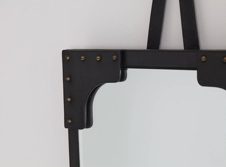 Gorgeous black leather mirror by Jacques Adnet with exposed brass screws and brass hanging hardware. Excellent for an entry, powder room, or on a gallery wall.  Mirror measurements: 21