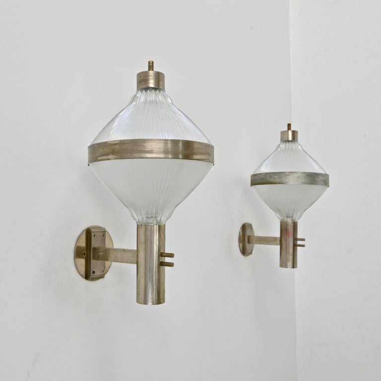 Pair of holophane glass and nickel Italian sconces by Studio B.B.P.R. for Artemide from the 1960s by Lodovico Barbariano di Belgiojoso, Enrico Peressutti, Ernesto N. Roger. Naturally aged. (2) E26 medium based sockets per sconce. Priced as a pair.