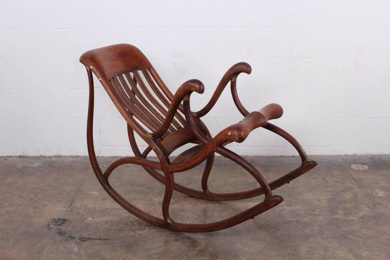 A beautifully crafted walnut rocking chair with bronze details. Crafted by David Crawford, 1988.