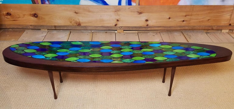 Georges Briard colors elliptical tiles set into metallic grout in an asymmetric elliptical insert offset in an asymmetric elliptical top on turned walnut legs.  The legs are similar to ones on a table by John Rothschild who made wonderfully