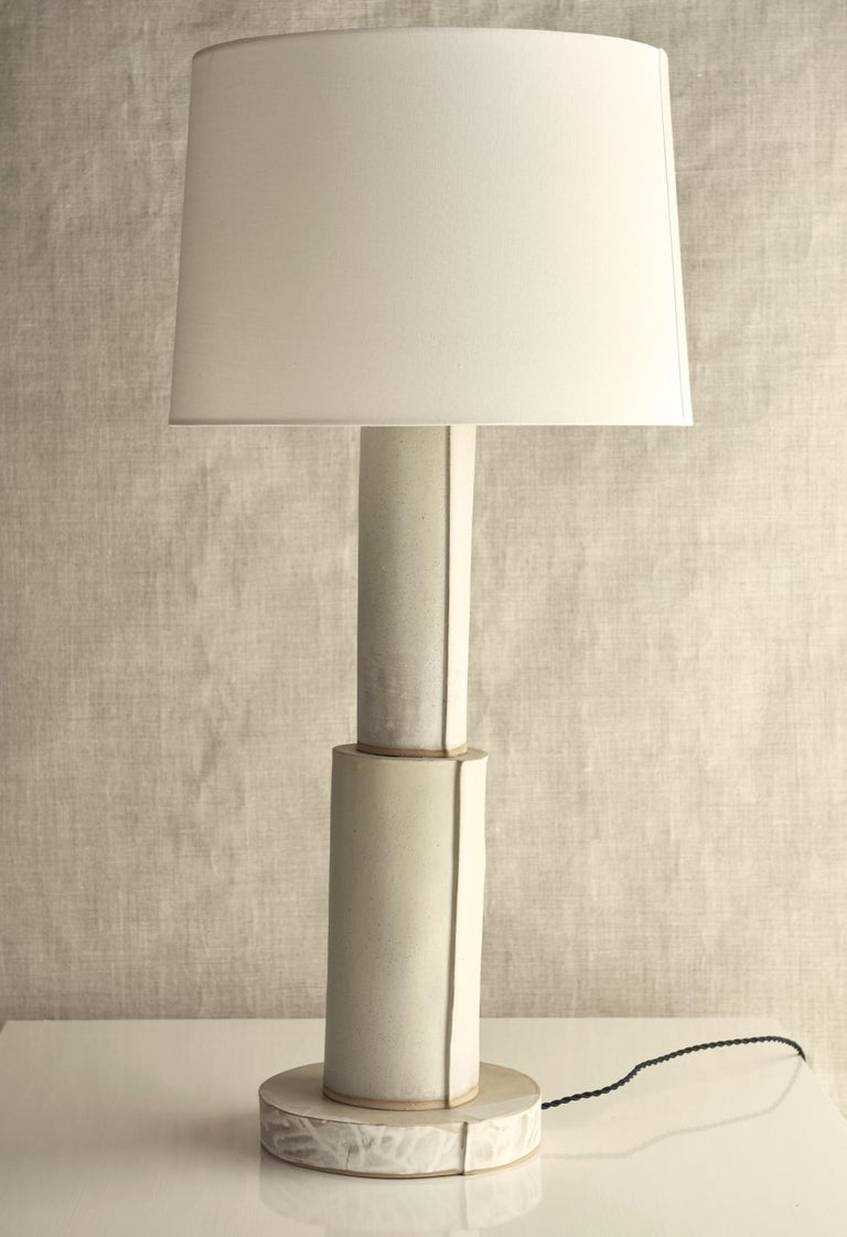 Description:  Handmade stoneware slab construction. Composed of three stacking cylinders. Lamps are individually crafted and one of a kind.  Finish:  Canvas white glaze. Antique brass fittings, dimmer switch and two cluster socket. Braided