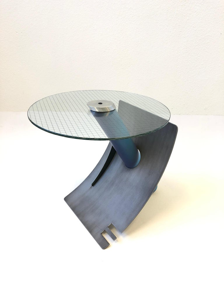 A spectacular studio Postmodern side table by Sculptor Michael Graham. The table is constructed of steel that's lacquered. The top cap is aluminum that hold the steel grid glass top to the base. The table is signed M. Graham and dated 1994 (see