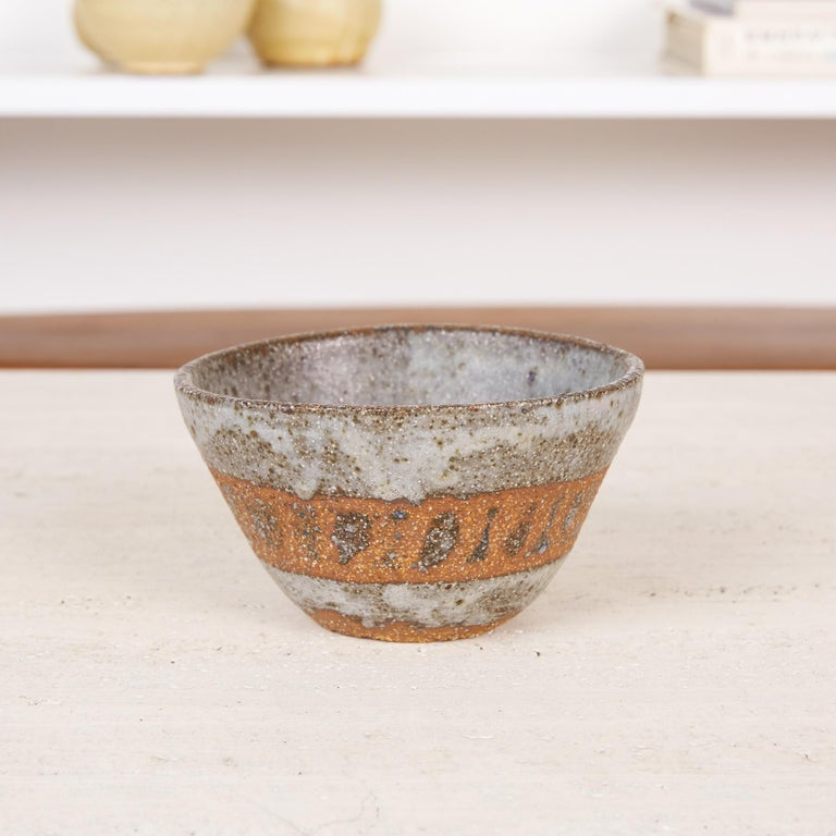 Studio pottery stoneware bowl. This small bowl is made from a red stoneware clay and features a striated icy gray glaze exterior accented by a band of unglazed clay detailing around the bowls diameter. The base of the interior of the bowl is