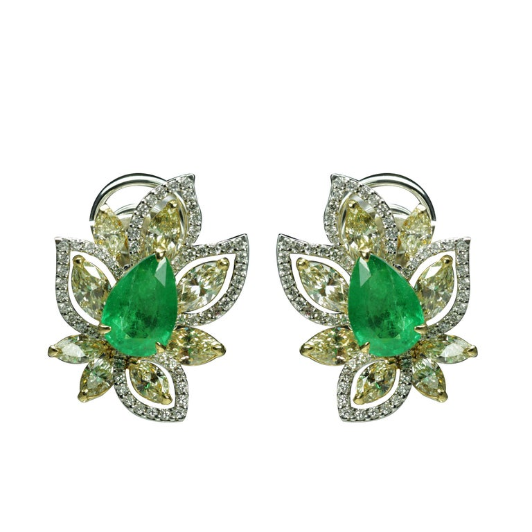 Emeralds, and white and yellow Diamond Earrings  A dazzling design coupled with calming shade of green gives this 18K white and yellow gold pair of earrings its tropical feel. Studded with emeralds, yellow brilliant cut marquise and round brilliant