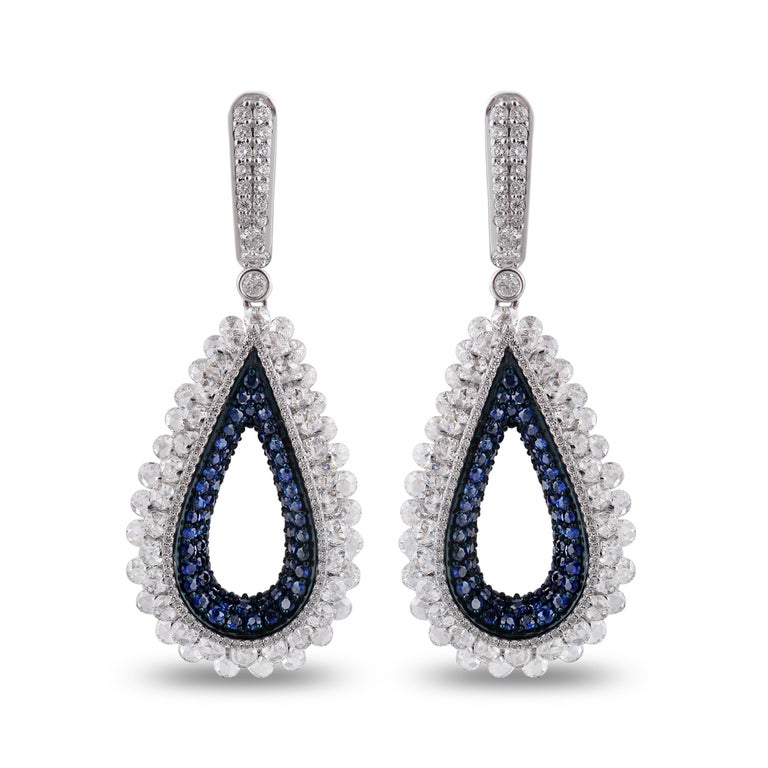 This teardrop-shaped pair of 18K white gold earrings featuring brilliant cut and rose cut diamonds will become a treasured part of your jewelry collection almost instantly. Adding charm to this style is a row of superior blue sapphires. The beauty