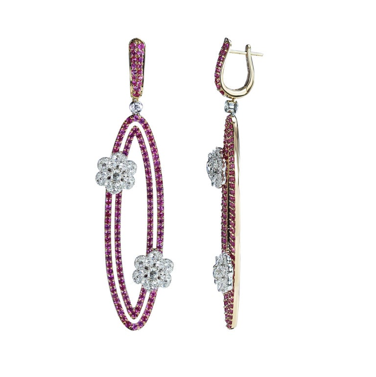 Diamond and Pink Sapphire Earrings  Geometry and nature inspirations come together in these earrings that are one for the ages. Beaded pink sapphires form oval loops that are brought together with floral motifs composed of round, oval, rose cut and