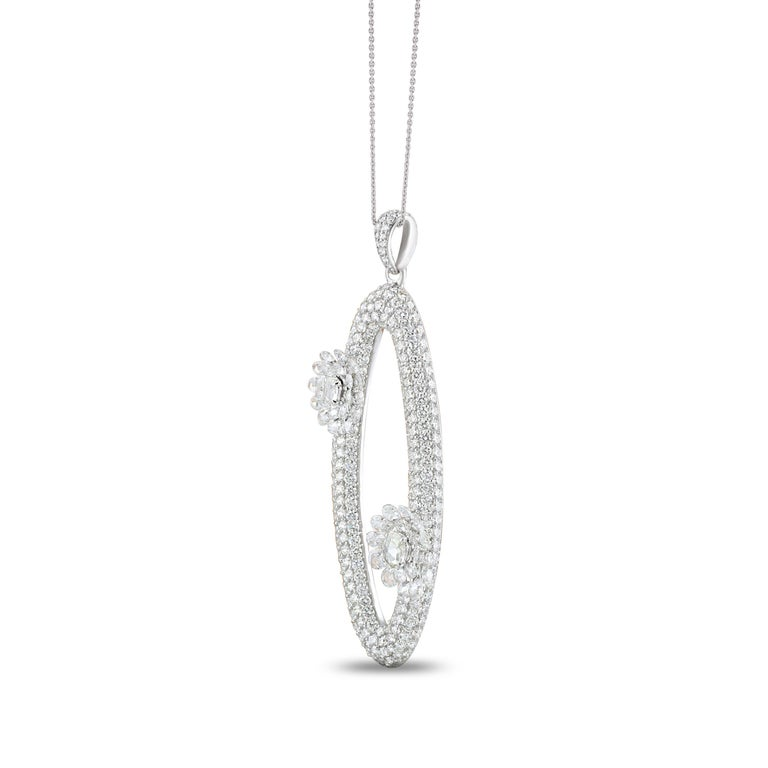 Pretty floral motifs adorn this pair of oval-shaped 18K white gold pendant that feature rose cuts and round brilliant cut diamonds set in a luxe drill and pavé setting. Generously studded with 306 stones, this can make any outfit come
