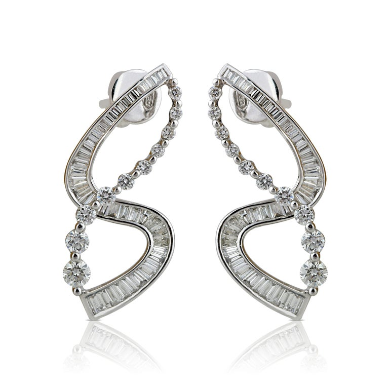 18K white gold and diamond earrings  Crafted with extreme precision in 18K white gold, these earrings with their unique design using round brilliant, baguettes and taper diamonds will perfectly pair with every look in your wardrobe. In a combination