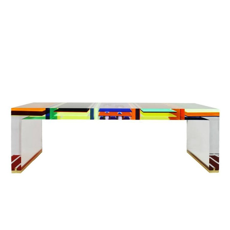 Rectangular coffee table designed by Milanese Studio Superego, made in multi-color and transparent plexiglass with seven centimetres thickness and feet of the legs finished in brass.
