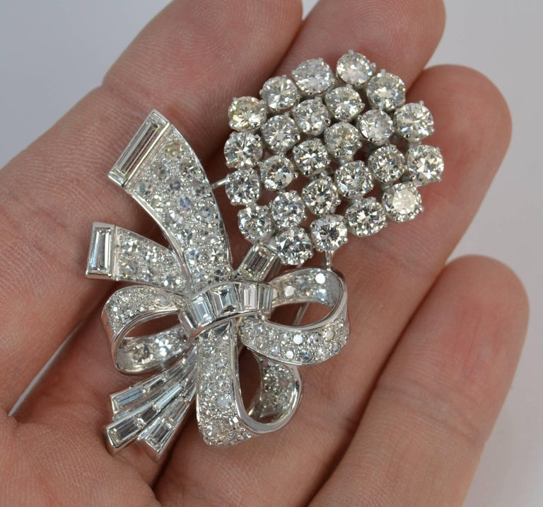 A beautiful 18 carat white gold and diamond floral shaped brooch.  A very striking example with multiple round brilliant and baguette cut diamonds throughout the bouquet, stem and ribbon surround. 25 diamonds set to the head, all between 3.8mm and
