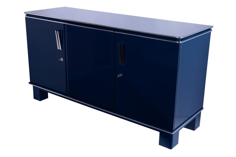 This stunning 1940s French Art Deco sideboard features a metallic cobalt blue lacquer finish with chrome detailing and fixtures. Three doors covering two drawers and a shelf on the left and a large shelf for storage to the right.
