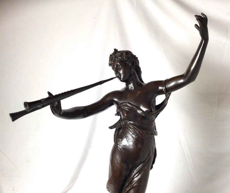 A patinated bronze figure of an Art Nouveau fiure of a woan with a flute. The sculpture with signature towards the base with a gilt bronze mount. Measures: 32 inches tall. Eugène Marioton, born in Paris on April 7, 1857, was a French sculptor
