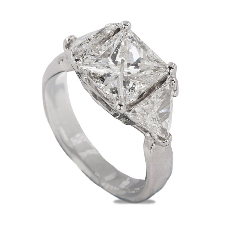 14k White Gold ring with GIA certified #2215318222 J color  SI1 clarity 3.03 carat princess cut diamond and 2 trillion cut diamonds weighing approximately 1.40 carats total weight.